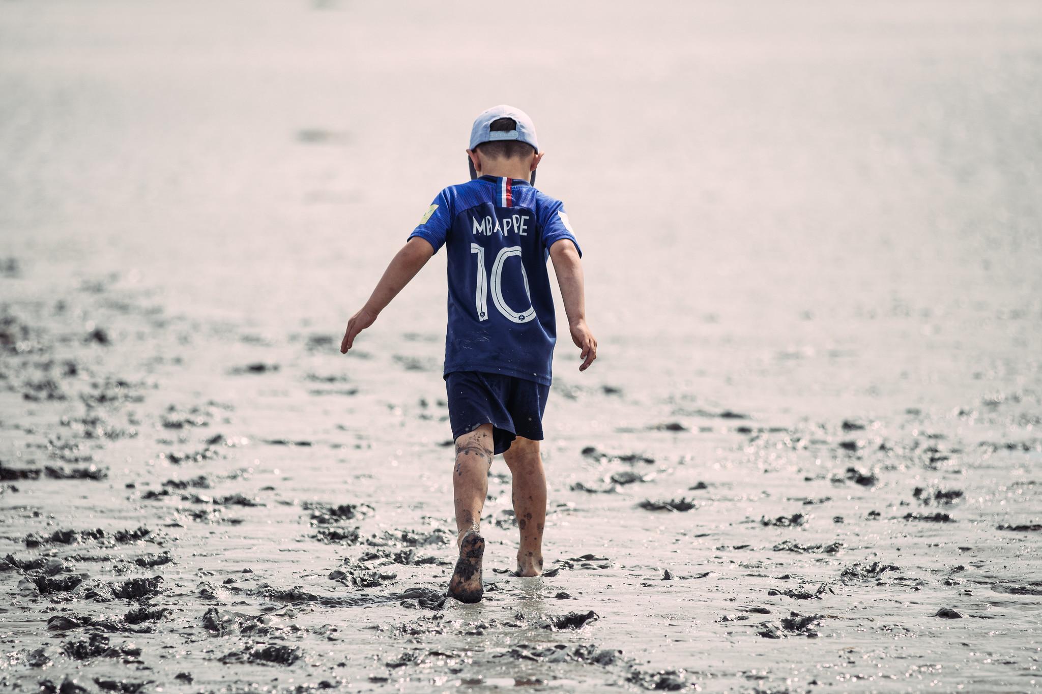 Photo nature : enfant dans la glaise de la baie du Mont-Saint-Michel (c) Mickael Mussard Photographe